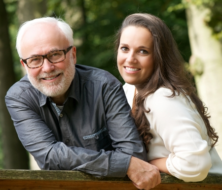 two women and one man: Portrit of a mature father and young daughter smiling outdoors