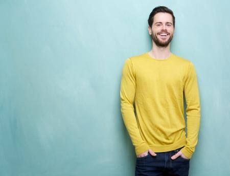 Portret van een knappe jonge man glimlachend tegen een blauwe achtergrond