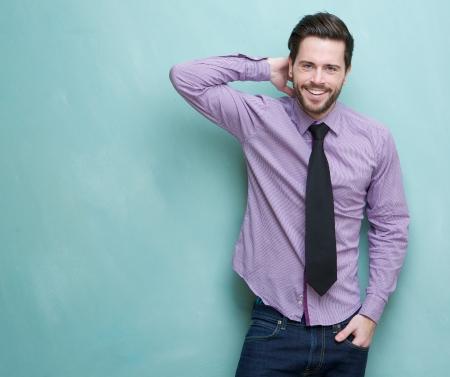 Portret van een jonge zakenman blij lachend tegen blauwe achtergrond Stockfoto