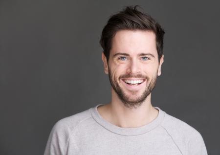 灰色の背景に笑みを浮かべて、幸せな若い男のクローズ アップの肖像画