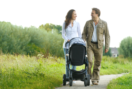 Portrait of a happy man and woman walking with baby pram outdoors 版權商用圖片