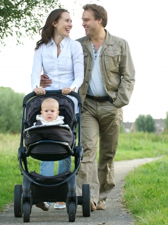 pram: Portrait of a happy mother and father smiling and pushing baby pram with child