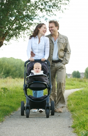 Portrait of happy male and female parents walking with their child in baby carriage  photo