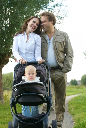 Portrait of a loving couple smiling together and walking with baby outdoors photo