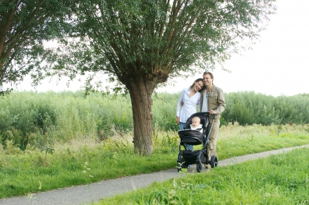 Horizontal portrait of a happy family walking outdoors with baby photo