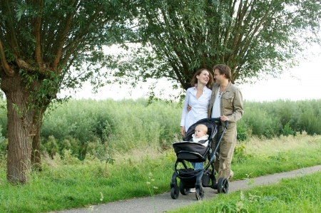 Portrait of a young mother and father walking outdoors with baby in pram photo