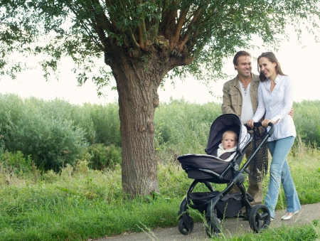 Portrait of a smiling mother and father walking outdoors and pushing baby in pram photo