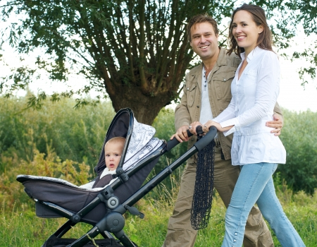 Portrait of a father and mother smiling outdoors and walking baby in pram photo