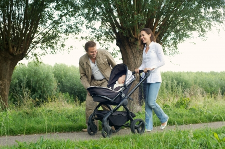 Portrait of a happy mother and father walking outdoors with baby in pram photo