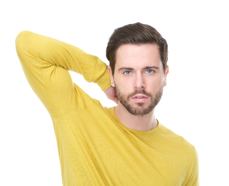 yellow shirt: Closeup portrait of a young man with yellow shirt looking at camera with serious expression and hand in hair Stock Photo