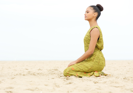 Horizontal portrait of a young woman sitting alone and meditating at the beach photo