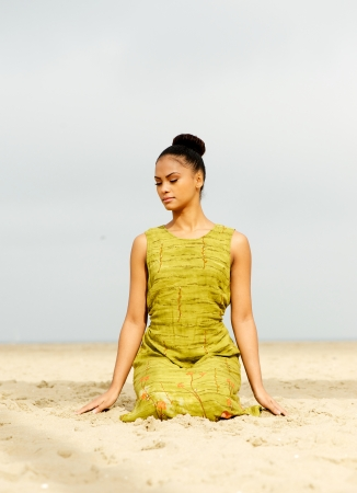 Portrait of a beautiful young woman meditating at the beach photo