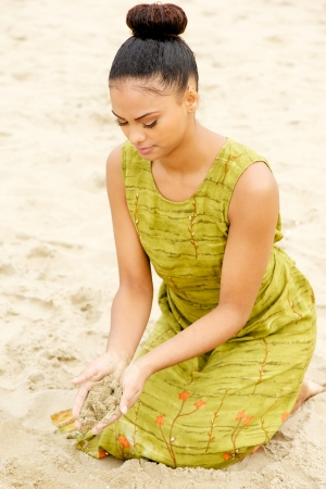 Portrait of a beautiful young woman sitting at the beach with sand flowing from hands photo