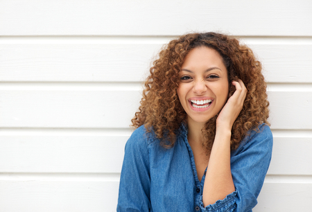 mixed race girl: Closeup portrait of a beautiful woman laughing with hand in hair