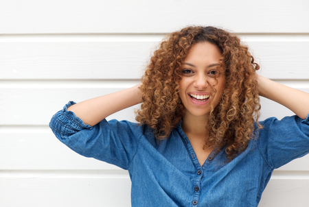Closeup portrait of a happy young woman smiling with hands in hair photo