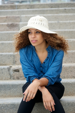 Portrait of a young woman wearing white hat sitting alone outdoors photo