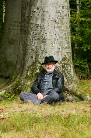 under tree: Portrait of an old man sitting under tree in the park