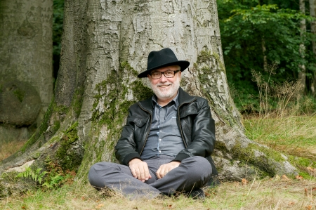 old man sitting: Portrait of a happy old man sitting under tree in the forest