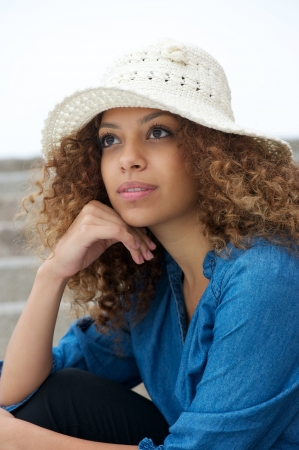 Close up portrait of a beautiful young woman sitting outdoors with hat photo