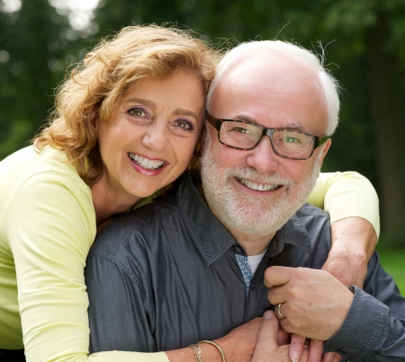 Close up portrait of a happy husband and wife smiling outdoors photo