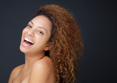 Close up portrait of a beautiful young woman with naked shoulders laughing  photo