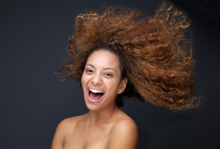 Close up portrait of an attractive young woman laughing with hair blowing Imagens