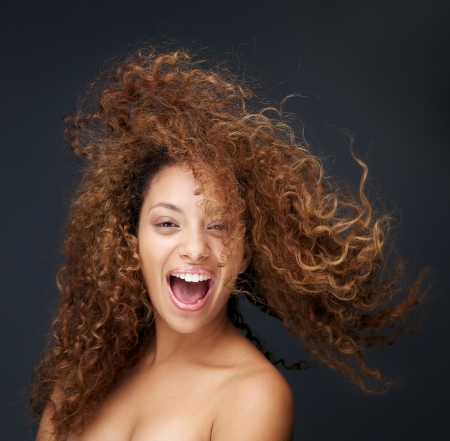 natural make up: Close up portrait of a fun and happy young woman laughing with hair blowing Stock Photo