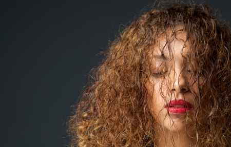 Close up portrait of a female fashion model with hair and eyes closed photo