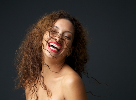 Close up portrait of an attractive young woman laughing with curly hair photo