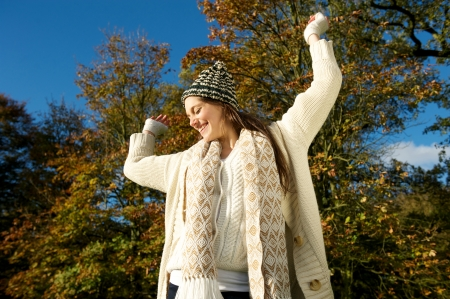 Portrait of a cheerful woman smiling outdoors on a sunny fall day with arms outstretched photo