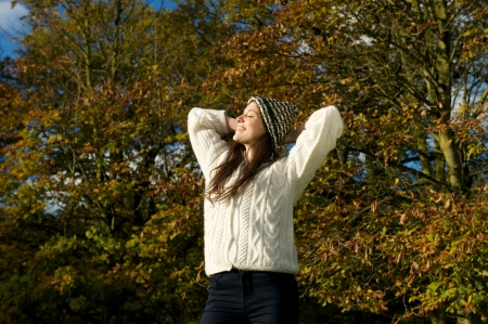 Portrait of a beautiful young woman relaxing outdoors and enjoying a sunny autumn day photo