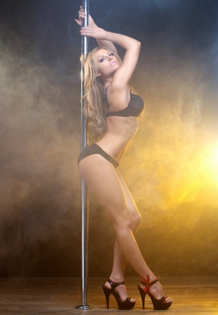 Full length portrait of a beautiful young female pole dancer  photo
