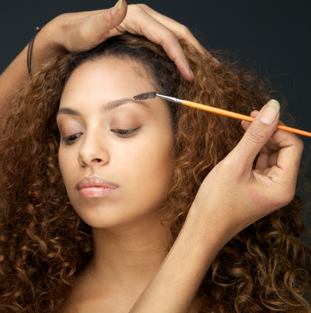 Close up portrait of a beautiful woman having eye make up application from professional photo
