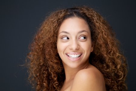 Close up portrait of a beautiful young woman with curly hair laughing and looking away photo