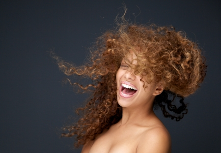 mixed race woman: Close up portrait of a happy young woman laughing with hair blowing