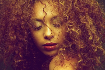 Horizontal beauty portrait of a young female fashion model with curly hair covering face photo