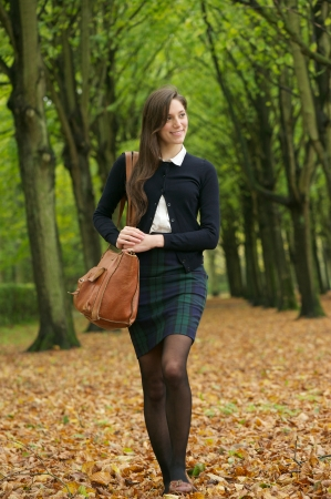 Full length portrait of a young woman walking in the park on an autumn day Stock Photo