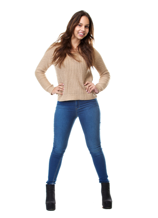 Full length portrait of a beautiful young woman standing on isolated white background smiling with hands on hips  photo