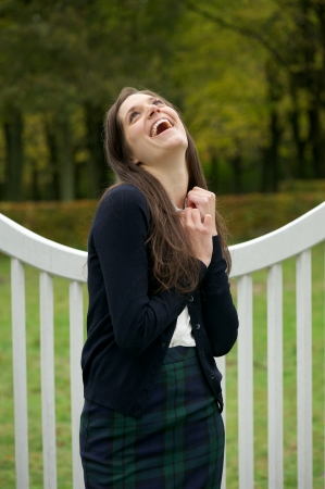 Portrait of a cheerful young woman laughing outdoors in the park