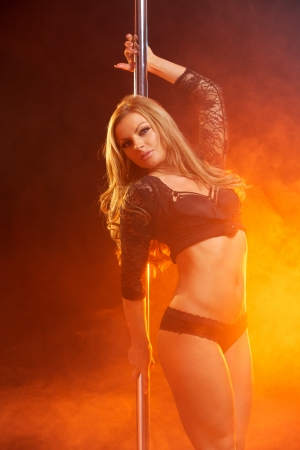 Portrait of a glamor girl in black lingerie pole dancing photo