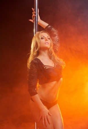 Portrait of an attractive female dancer with dance pole photo