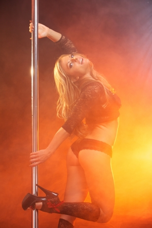 Portrait of a sensual blond hair woman pole dancing  photo