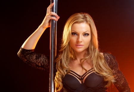 Close up portrait of a beautiful blond woman with dance pole photo