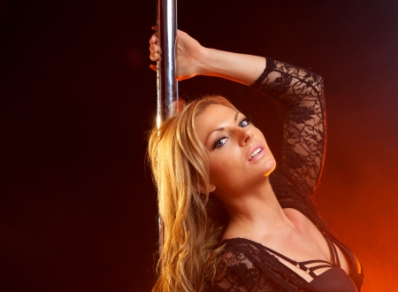 Close up portrait of a pretty blond woman pole dancing photo