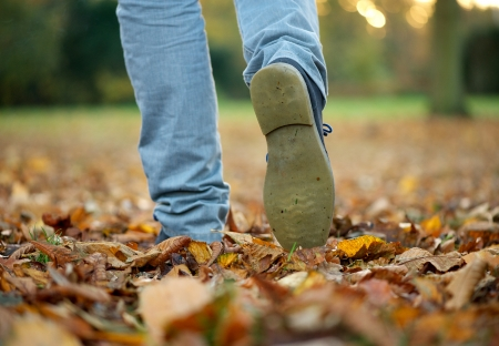 Male walking with boots on autumn leaves photo