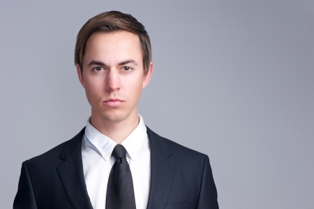 Close up portrait of a serious business man face isolated on gray background photo