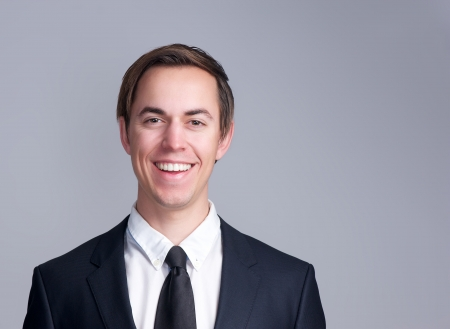 Close up portrait of a smiling business man in suit isolated on gray background photo
