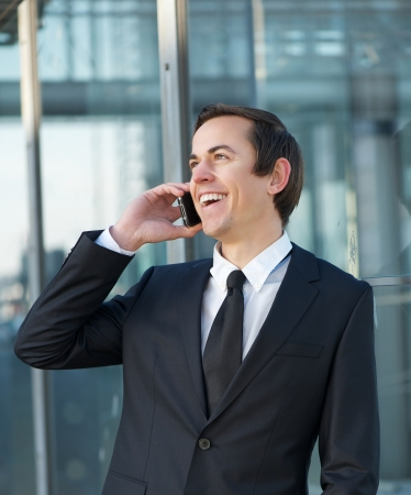 Close up portrait of a businessman talking and laughing on mobile phone   photo