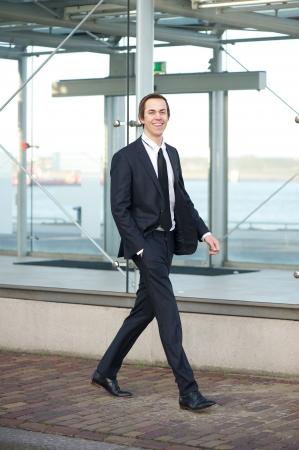 Full length portrait of a handsome young businessman walking in the city photo