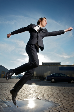 Portrait of a businessman jumping over puddle of water on the street photo